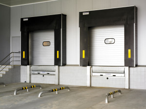 Loading dock with hinged lip dock leveller
